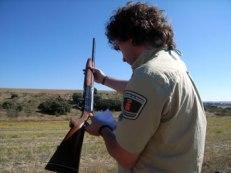 Agente forestal inspeccionando una escopeta de caza.