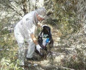 Voluntario recogiendo residuos en el arroyo Ladrón.