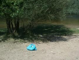 Una bolsa de basura en la orilla del río Alberche. (Foto: Diego Gil Muñoz).